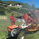 Tenzin showing the other monks how to ride the power tiller