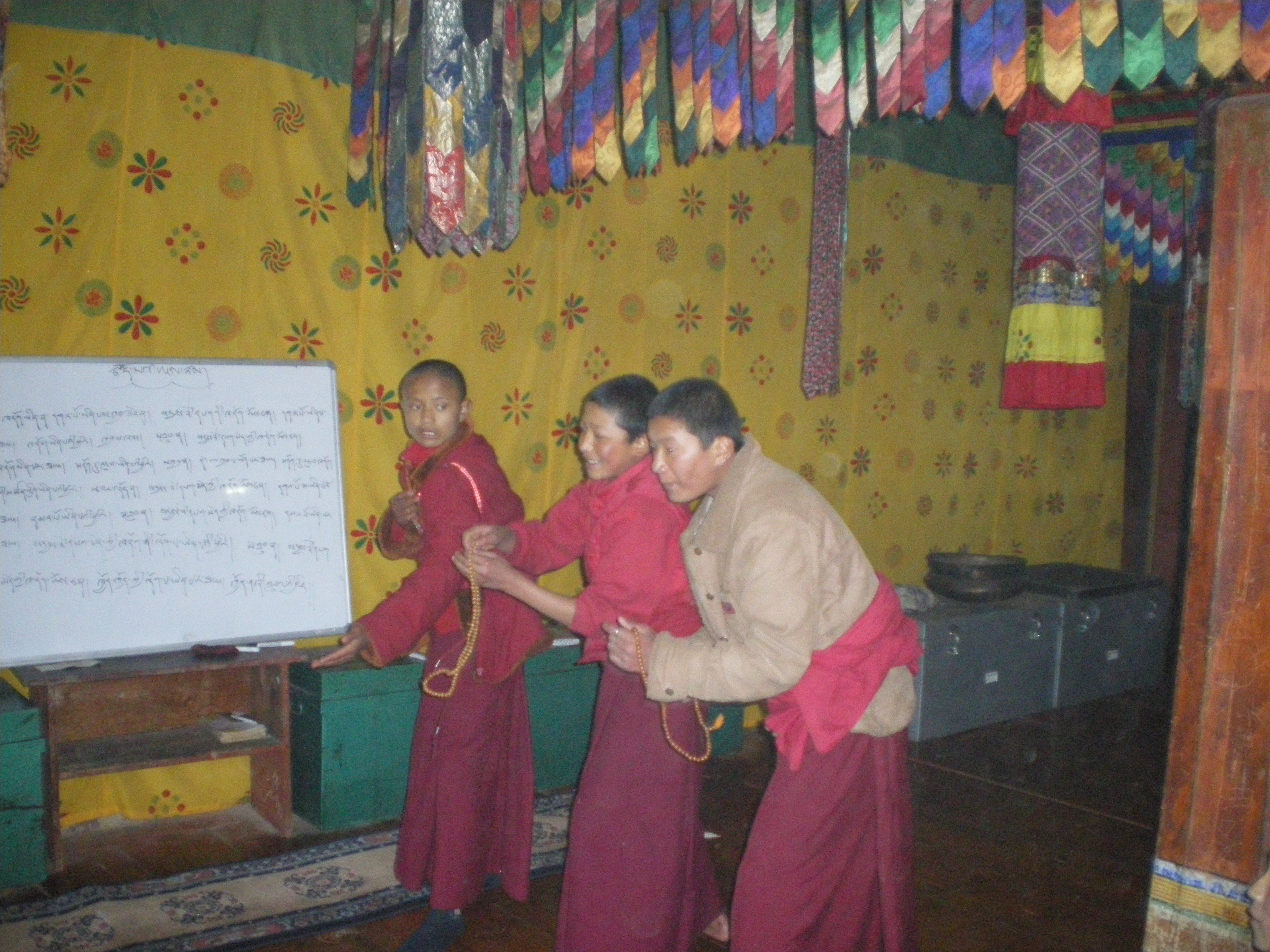 The monks learning the correct placement of the hands and mala beads.